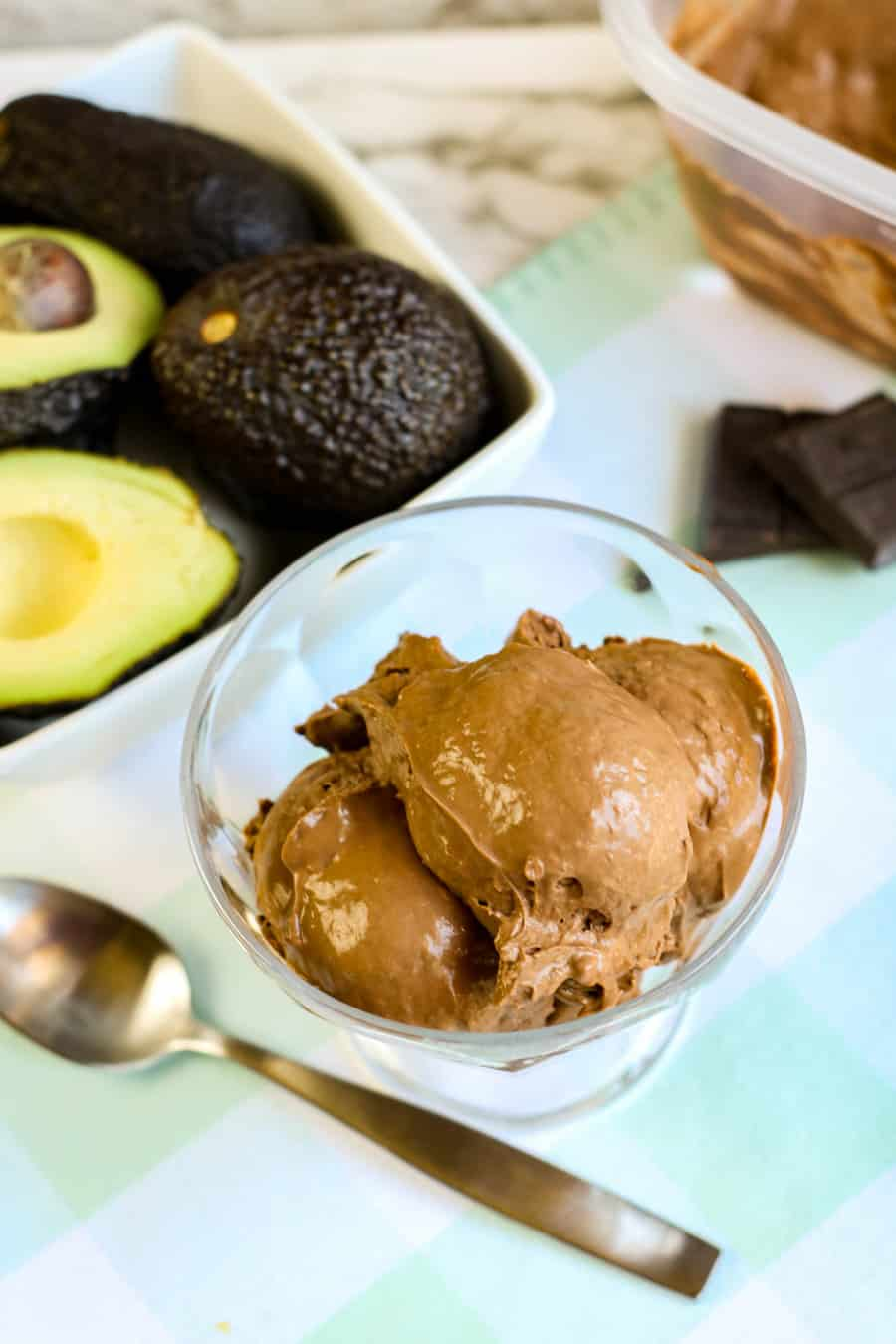chocolate avocado ice cream in glass dish with avocados and chocolate in the background