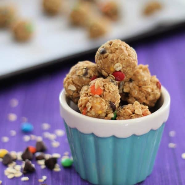 no bake monster cookie balls in blue container purple background